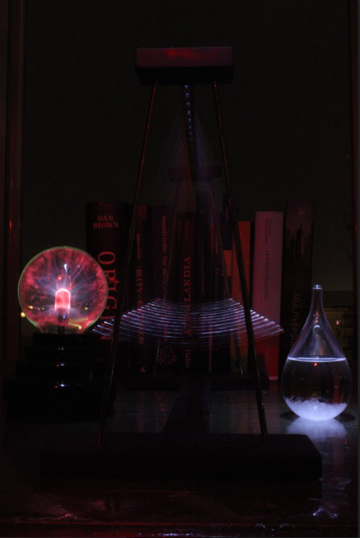 A photograph of a pendulum with a glowing red globe on the left side and a teardrop-shaped flask with water on the right side. In the background is a bookshelf filled with books.